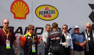 President of Shell Commercial Fuels and Lubricants Americas, Istvan Kapitany, greets driver of the No. 12 Team Penske Chevrolet, Will Power, during pre-race festivities on Sunday, October 6, 2013 at the Shell and Pennzoil Grand Prix of Houston. During the race weekend, Shell showcased its motorsports technical alliances to the racing community and consumers, highlighted by Pennzoil Ultra 0W-40 full synthetic motor oil, which was used on the track all weekend, and is the same oil consumers can purchase and use on the road.(Photo Credit: Pennzoil/Kinnon Marshall)